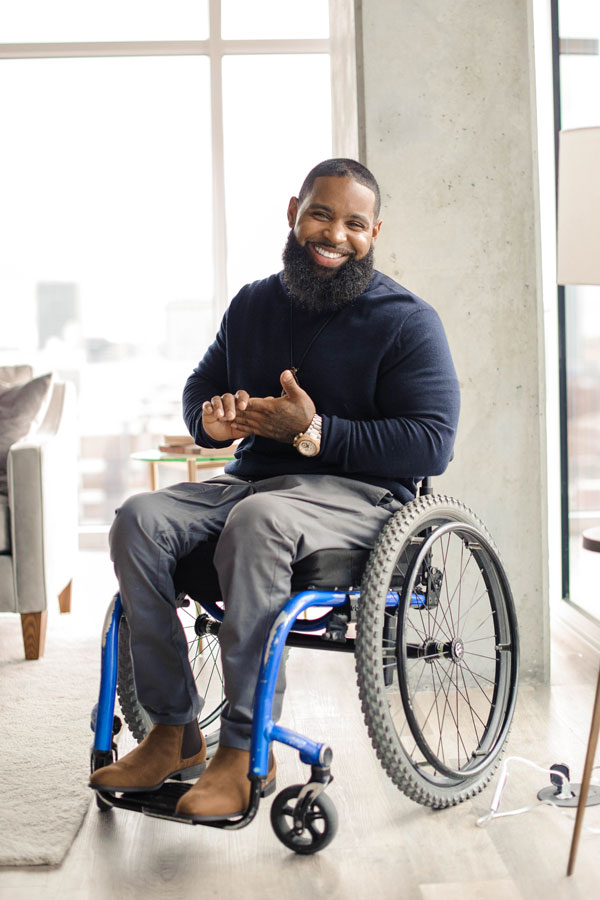 Wesley Hamilton sitting in his wheelchair, smiling. He is wearing a blue long-sleeve shirt, grey slacks and brown boots.