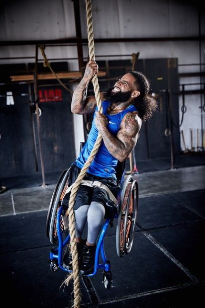 Wesley in a blue shirt lifting himself and his chair up a rope.